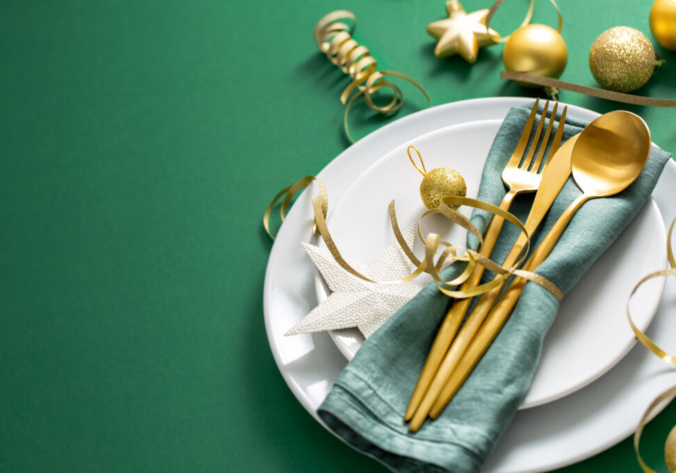 Christmas Flat Lay Background. Gold Cutlery with Bubbles served on napkin on plate on Green Background. Minimalistic design. Copy Space. Horizontal. Christmas concept.